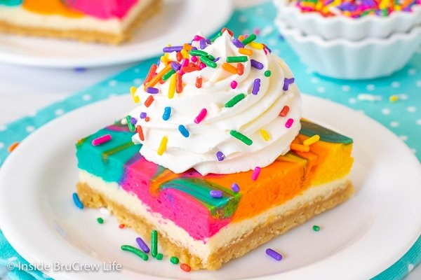 A white plate on a teal towel with a square of rainbow cheesecake bars topped with Cool Whip and sprinkles