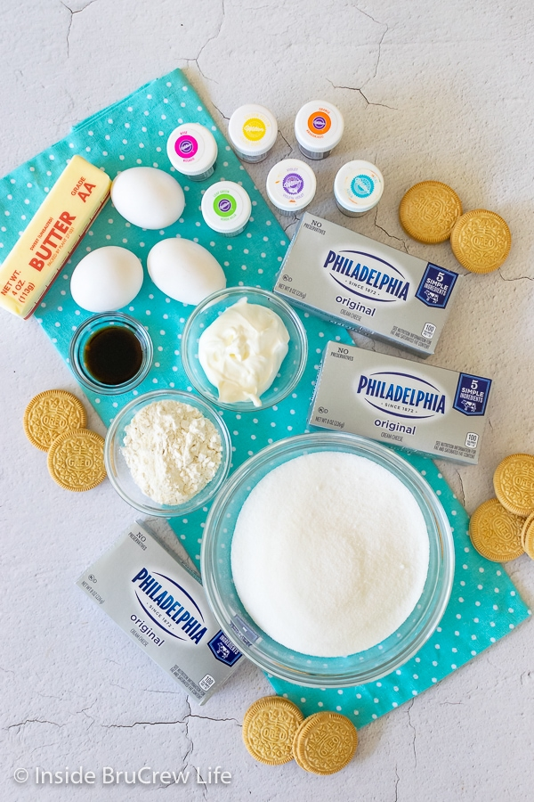 Overhead picture of the ingredients needed to make rainbow vanilla cheesecake bars on a teal towel