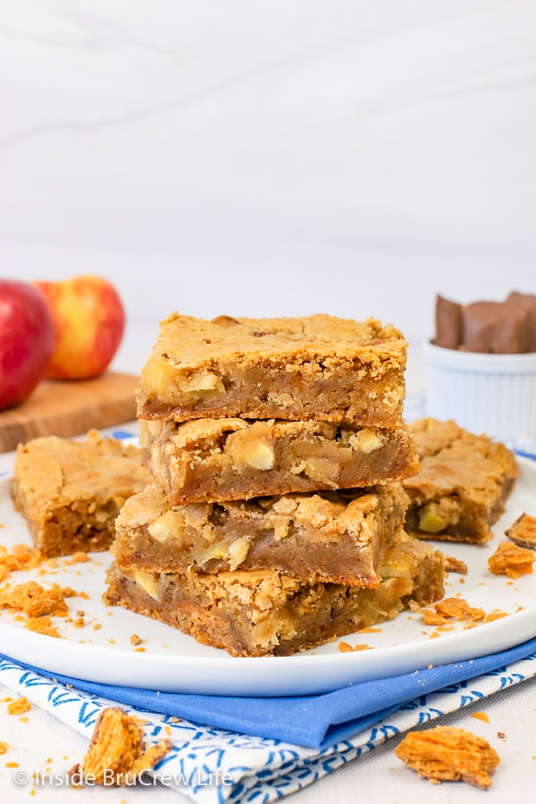 A white plate with stacks of apple blondies on it.