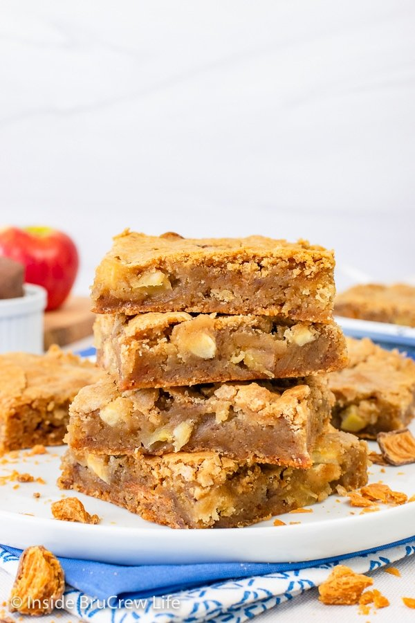 Four apple blonde brownies stacked on a white plate.