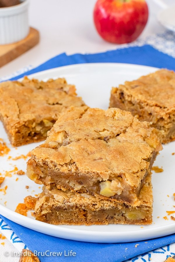 A white plate with squares of butterfinger apple blondies on it.