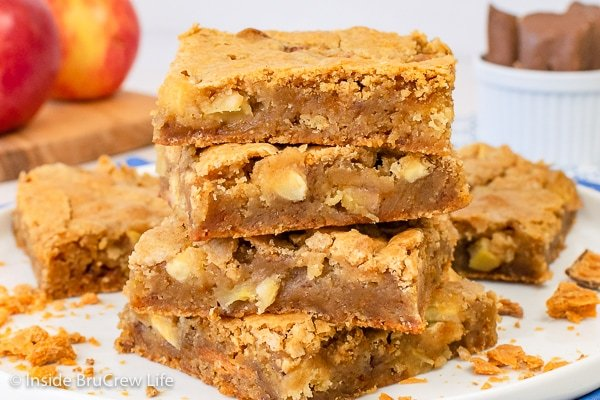 A white plate with four butterfinger apple blondies stacked on it and crushed candy bars around it.