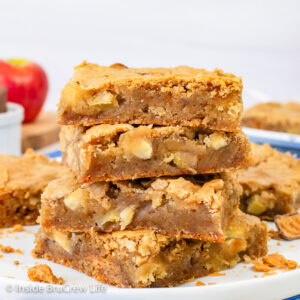 A stack of four apple blondies on a white plate.