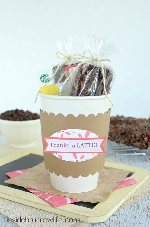 A white cardboard coffee cup stuffed with cappuccino chip granola bars and a coffee gift card