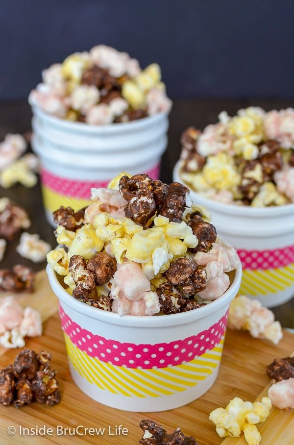 A white bowl overflowing with chocolate, strawberry, and banana popcorn and more filled bowls in the background