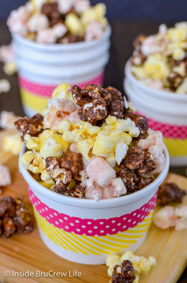 A white paper cup with pink and yellow stripes filled with banana split popcorn with more bowls behind it