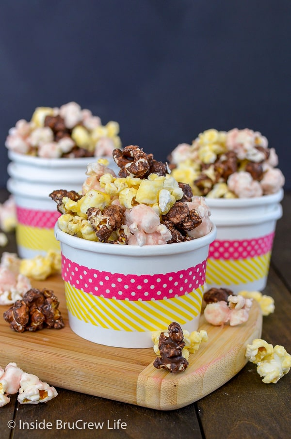 Three white bowls with pink and yellow stripes filled with banana split popcorn