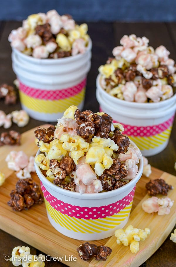 Three white bowls filled with chocolate, banana, and strawberry flavored popcorn