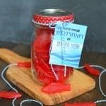 A mason jar filled with swedish fish and a printable birthday tag tied on the lid