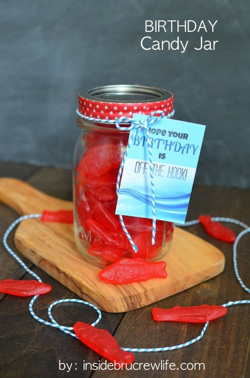 A mason jar filled with Swedish fish  with a printable birthday tag tied on with blue and white twine