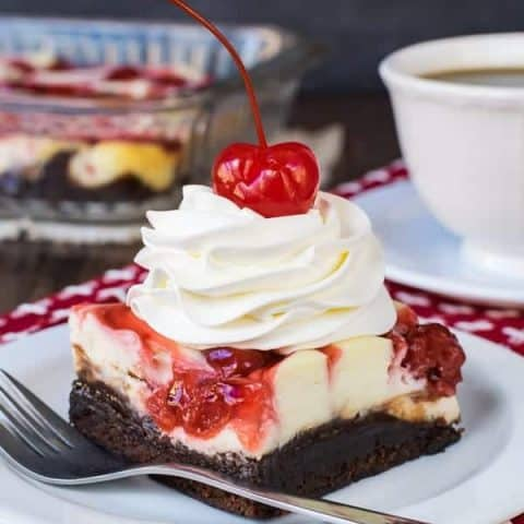 A white plate with a square of cherry cheesecake brownies topped with cool whip and a cherry