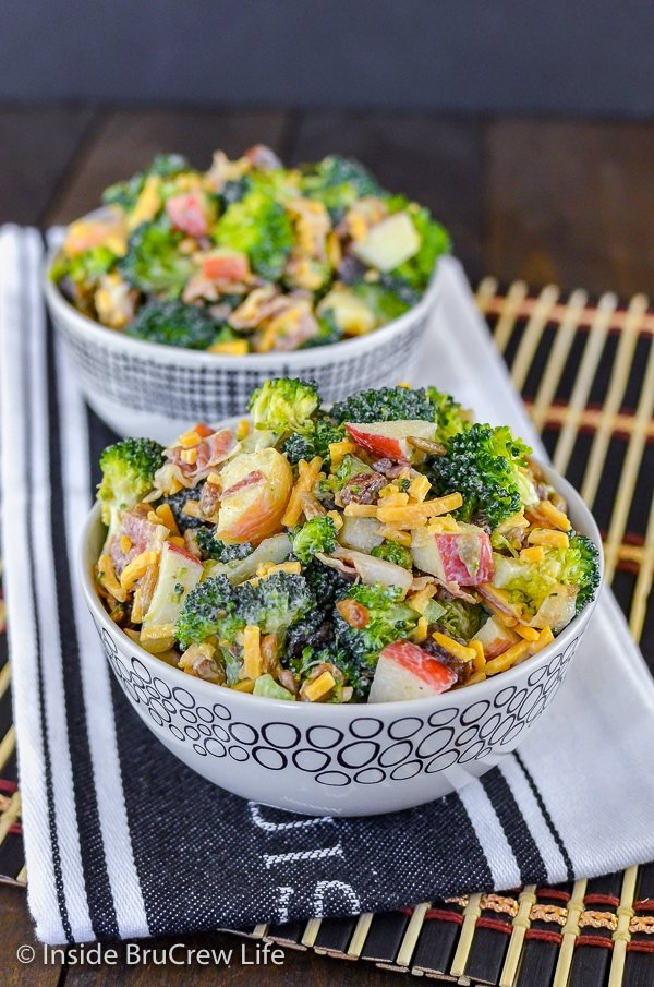 A white bowl filled with broccoli apple salad and another bowl behind it