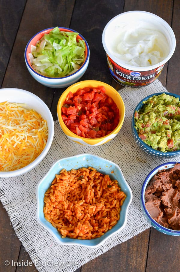 Overhead picture of seven bowls of toppings for seven layer burritos