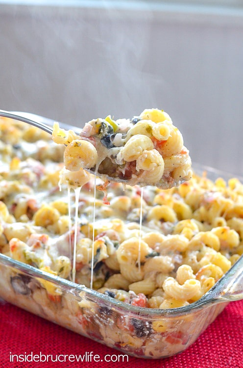 A spoonful of cheesy pasta lifted up from a pan of veggie supreme pasta bake