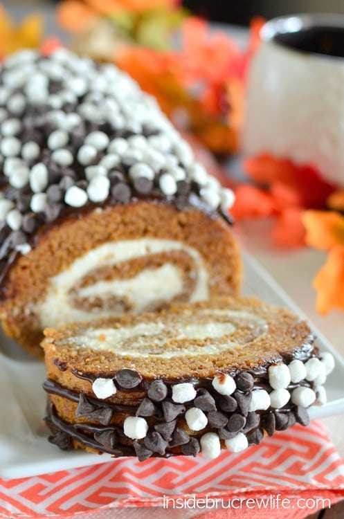 S'mores Pumpkin Roll - chocolate drizzles and marshmallow frosting adds a fun twist to the classic pumpkin roll. Easy recipe to make for dinners this fall. #pumpkin #cakeroll #fall #smores #thanksgiving