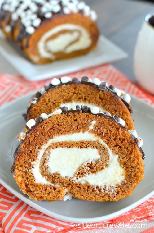 S'mores Pumpkin Roll - marshmallow frosting and chocolate drizzles give the classic pumpkin roll a delicious flair. Easy recipe to make for dinners this fall. #pumpkin #cakeroll #fall #smores #thanksgiving