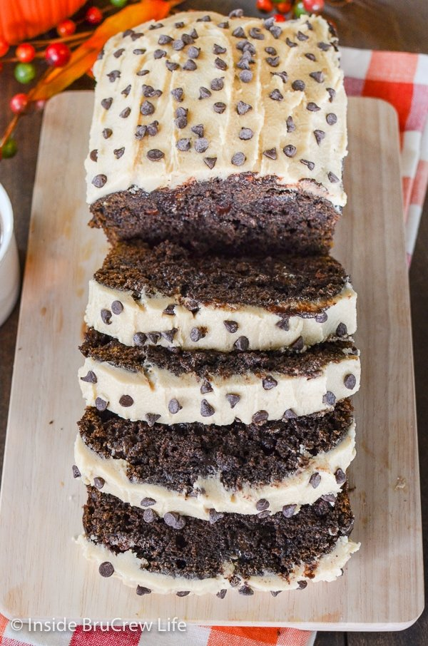 A wooden cutting board with slices of chocolate loaded pumpkin bread topped with caramel frosting.