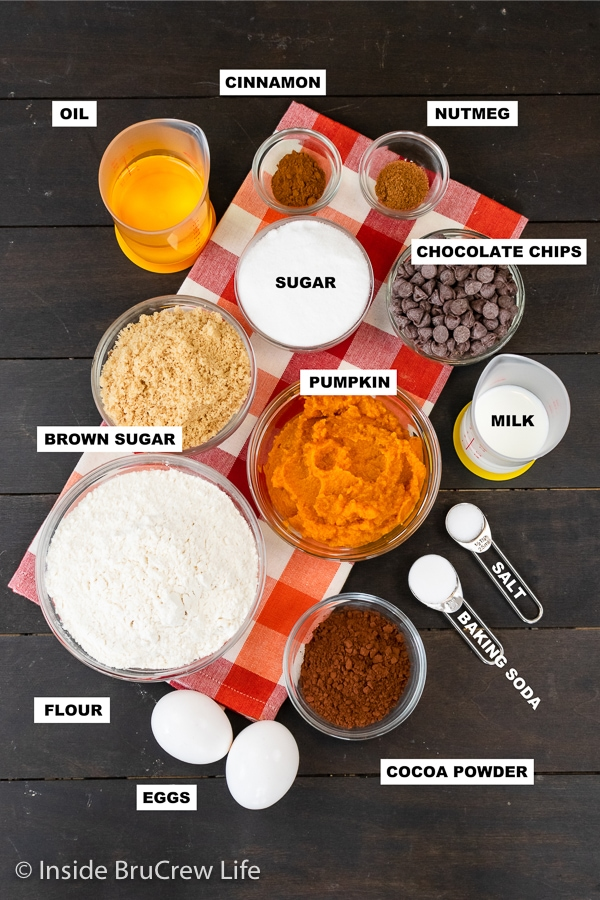 A wooden board with bowls of ingredients needed to make a chocolate pumpkin bread.