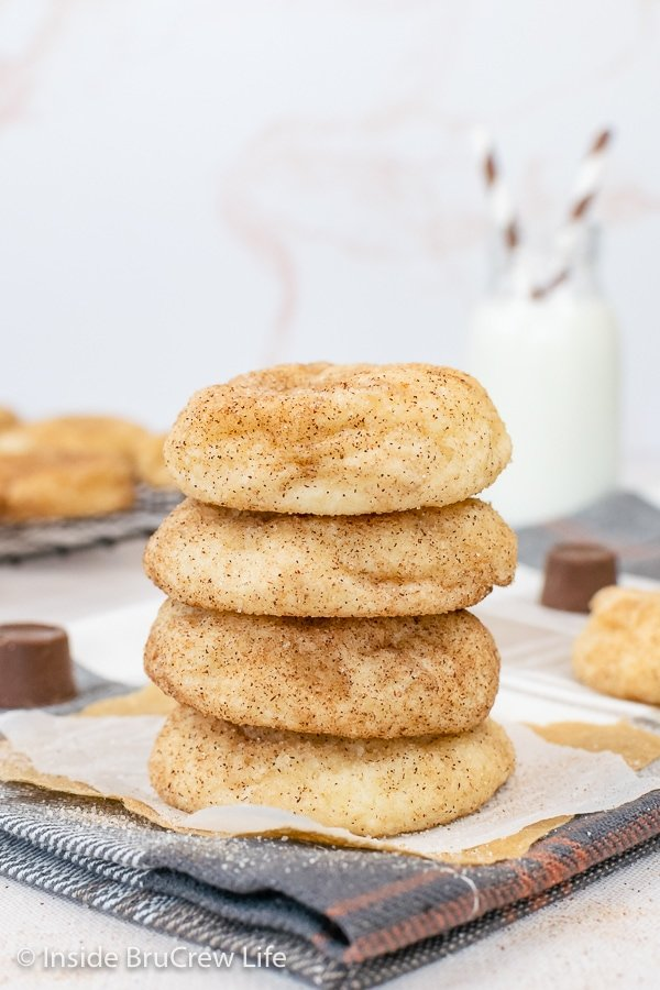 Four snickerdoodle cake mix cookies stacked on a white paper.