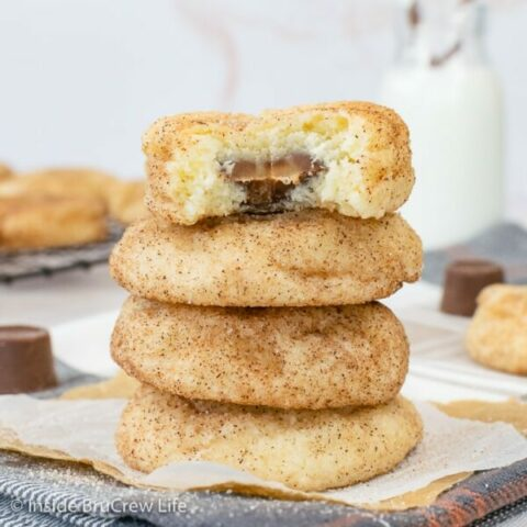 A stack of four cinnamon Rolo cookies stacked on top of each other. One cookie has a bite out of it showing the caramel center.
