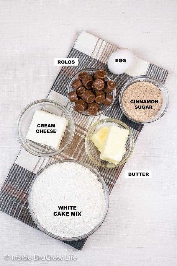 A white board with bowls of ingredients to make caramel stuffed snickerdoodle cookies.