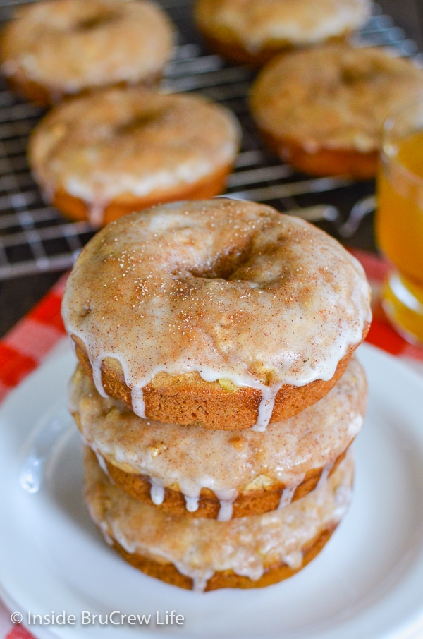 Three cinnamon apple donuts on a white plate with more donuts behind them