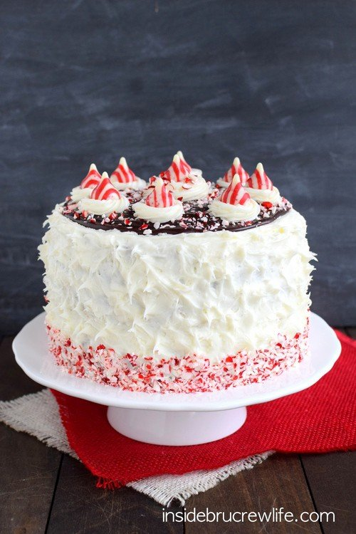Candy Cane Chocolate Cheesecake Cake - layers of cake, cheesecake, and peppermint frosting makes this holiday cake so pretty and delicious! Great recipe for holiday parties!