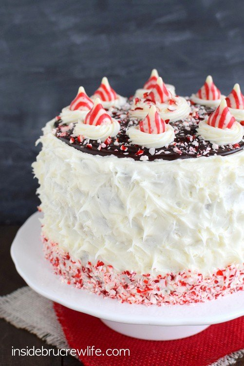 Candy Cane Chocolate Cheesecake Cake - fluffy peppermint frosting and candy cane chunks cover the layers of chocolate cake and cheesecake!  Such a great cake for holiday parties!