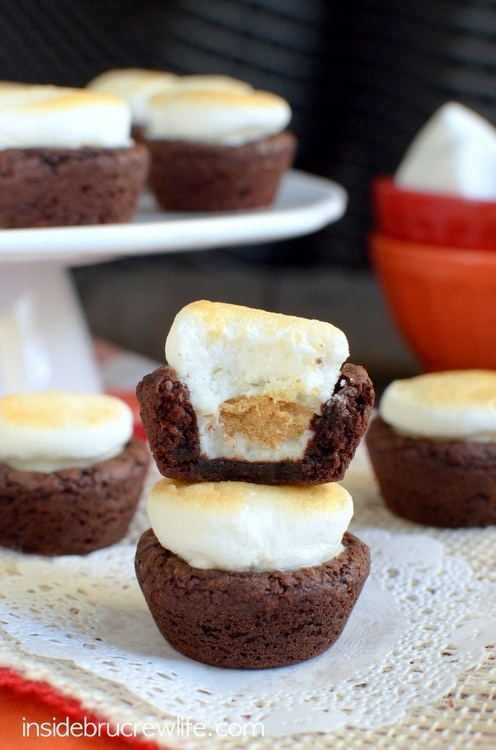 Mini brownie bites stuffed with peanut butter cups and topped with a toasted marshmallow for a fun s'mores twist!