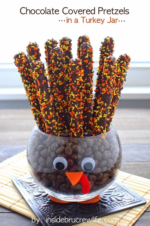A clear jar decorated to look like a turkey filled with chocolate covered pretzels and candies