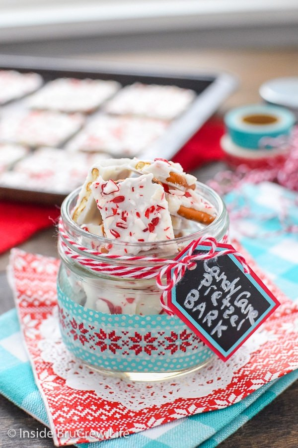 A clear jar filled with pieces of candy cane pretzel bark and tray of more bark behind it