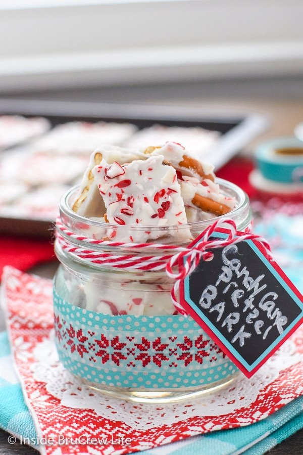 A red and teal towel with a clear jar filled with candy cane pretzel bark on it