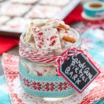 A clear jar filled with candy cane pretzel bark on a red and teal towel