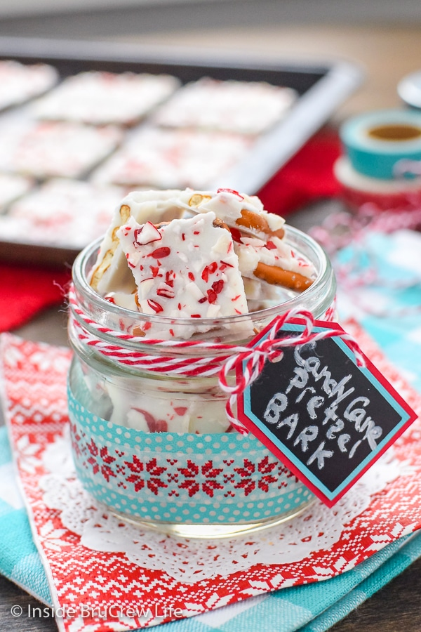 A clear jar filled with candy cane pretzel bark on a red and blue napkin