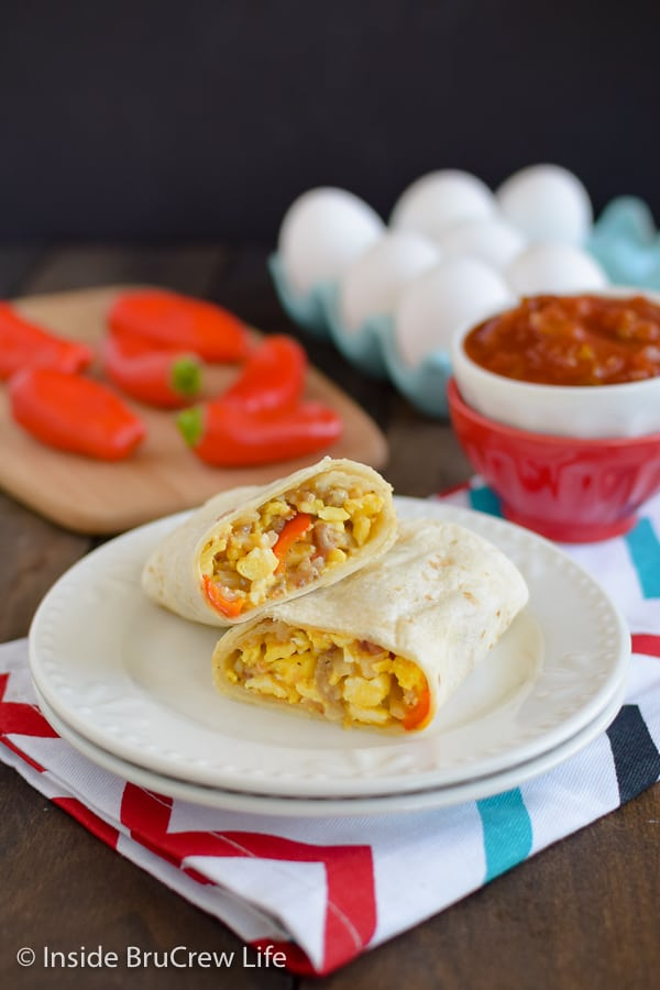 An egg burrito cut in half and stacked on a white plate with a bowl of salsa beside it.