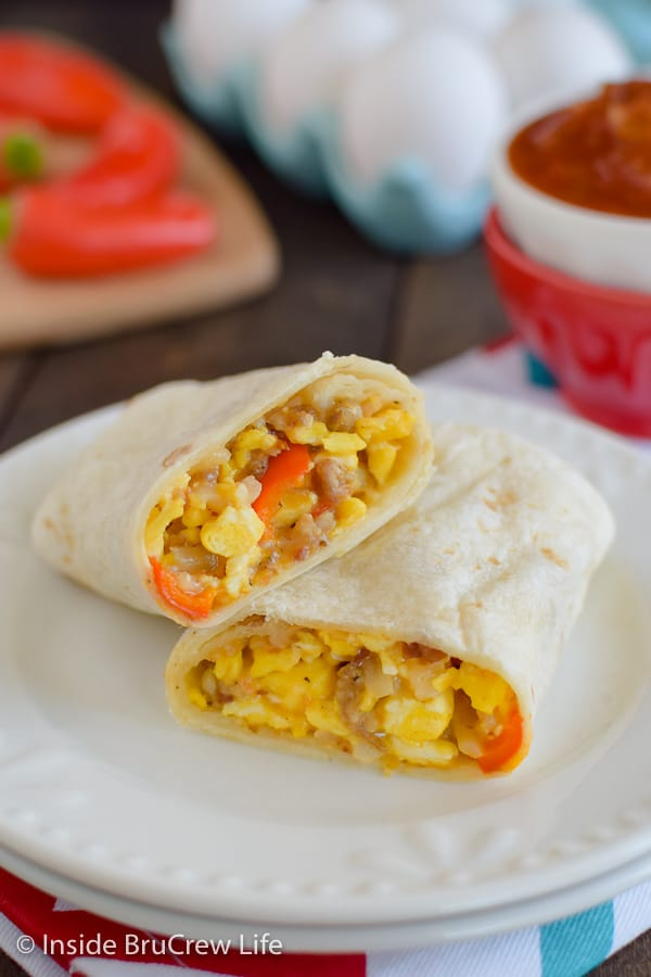 A white plate with two halves of a breakfast egg burrito stacked on it.
