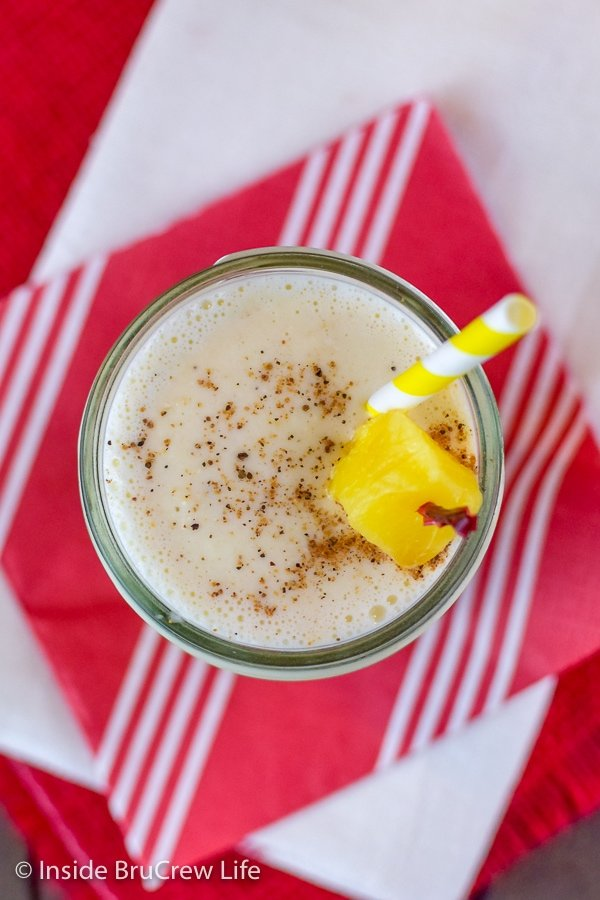 Overhead picture of a clear glass filled with vanilla pineapple smoothie on a red napkin