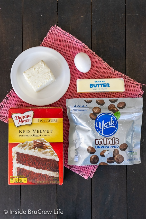 A dark board with ingredients to make red velvet peppermint pattie cookies