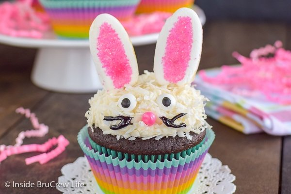 A coconut topped cupcake decorated with marshmallow ears and a candy face to look like an Easter bunny