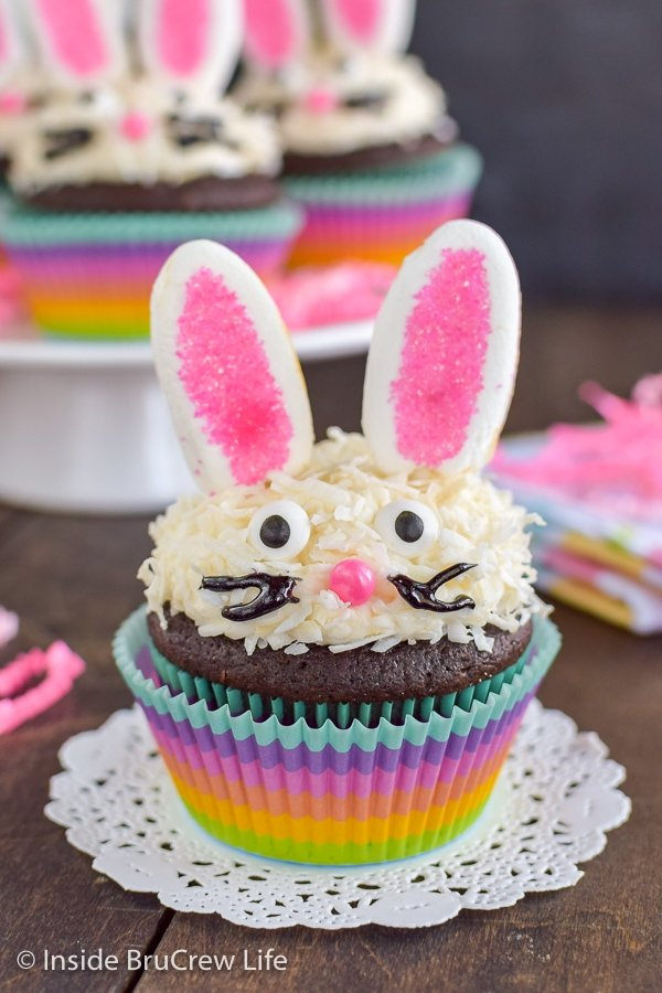 A chocolate bunny cupcake in a rainbow colored liner topped with vanilla frosting, coconut, marshmallow ears, and a candy face