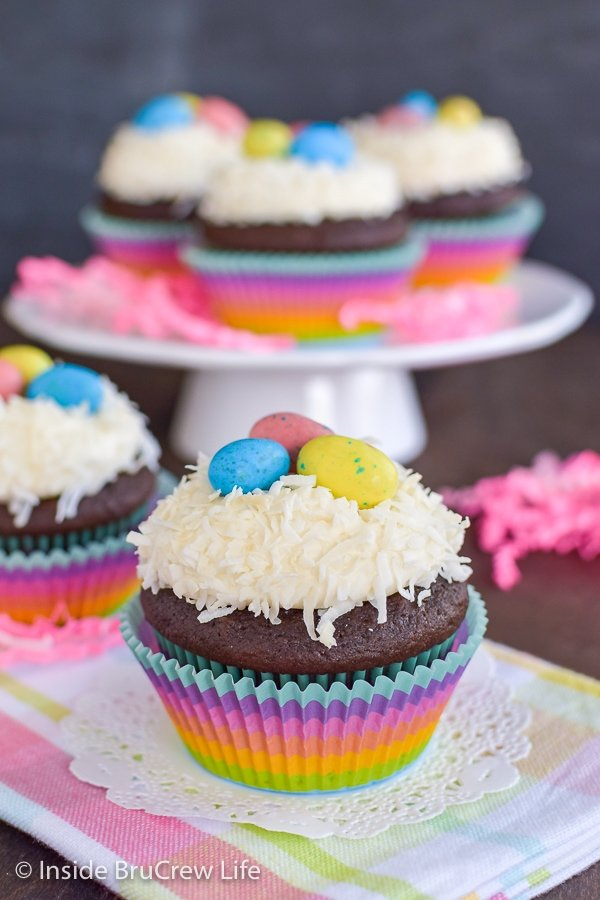 Two chocolate cupcakes topped with vanilla frosting, coconut, and candy eggs with more cupcakes behind them