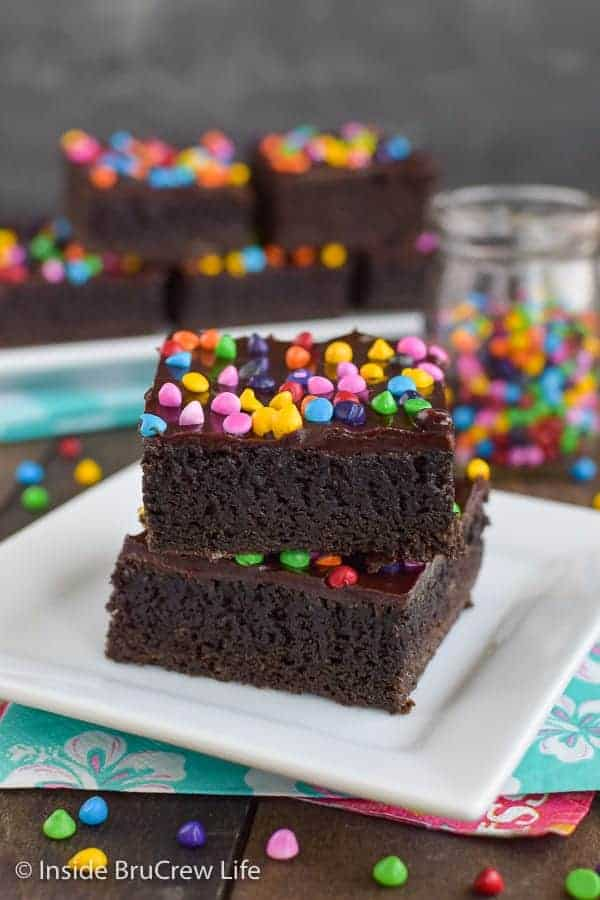 Frosted Rainbow Chip Brownies - these dark chocolate homemade brownies are topped with a fudge frosting and rainbow chip sprinkles. They are such a fun treat for dessert or bake sales.