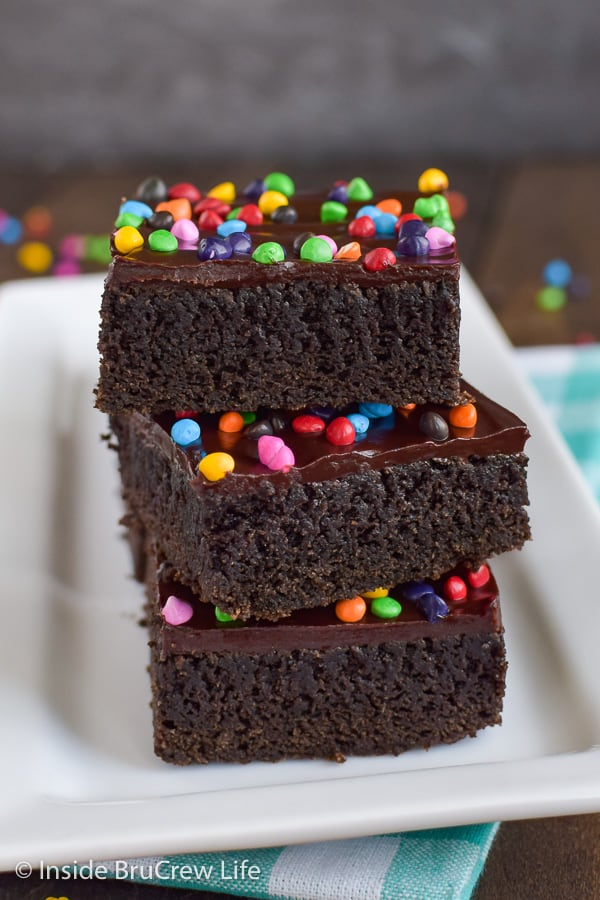 Frosted Rainbow Chip Brownies - these dark chocolate brownies get a fun and delicious twist with dark chocolate frosting and rainbow sprinkles. Great copycat cosmic brownies recipe for bake sales or dessert.