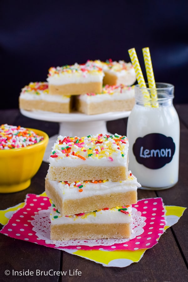 Lemon Sugar Cookie Bars - easy lemon cookies topped with a fluffy lemon frosting. Make this easy recipe when you need a fun dessert! #sugarcookiebars #lemonbars #lemoncookies #lemonfrosting #homemade #easydessert