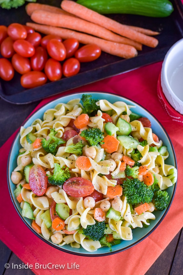 Overhead picture of a big bowl on an orange towel filled with veggie pasta salad