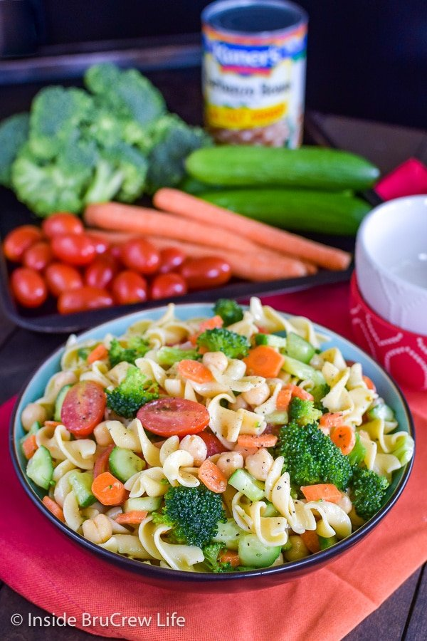 A big bowl on an orange towel filled with veggie pasta salad and a tray of whole vegetables behind it