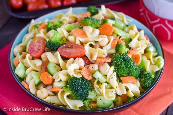 A bowl of veggie pasta salad sitting on a red orange towel