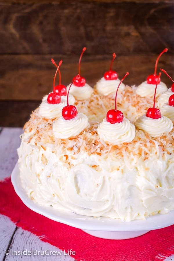 A picture of the side of a pina colada bundt cake decorated with frosting, coconut, and cherries