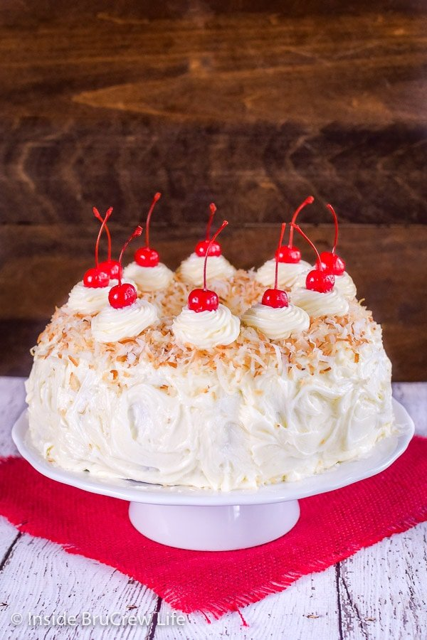 A frosted pina colada bundt cake on a white cake plate decorated with toasted coconut and maraschino cherries