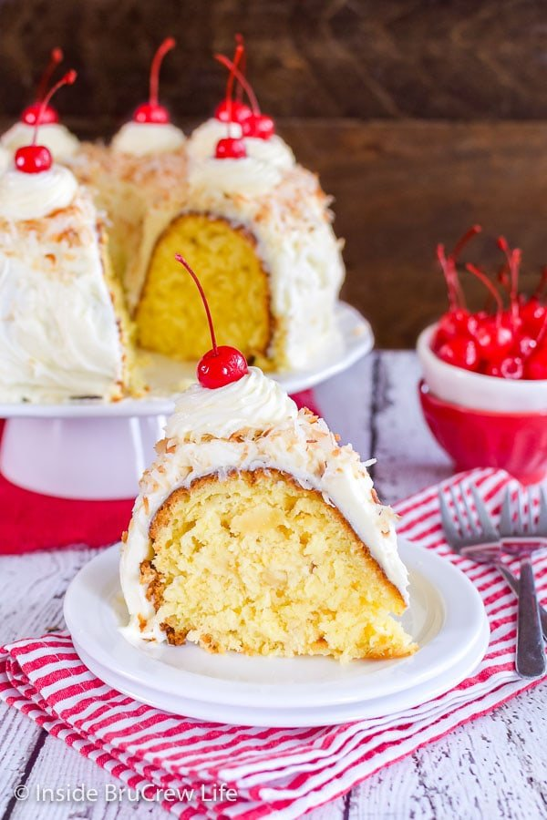 A slice of pina colada bundt cake on a white plate with a bowl of cherries and the rest of the cake behind it